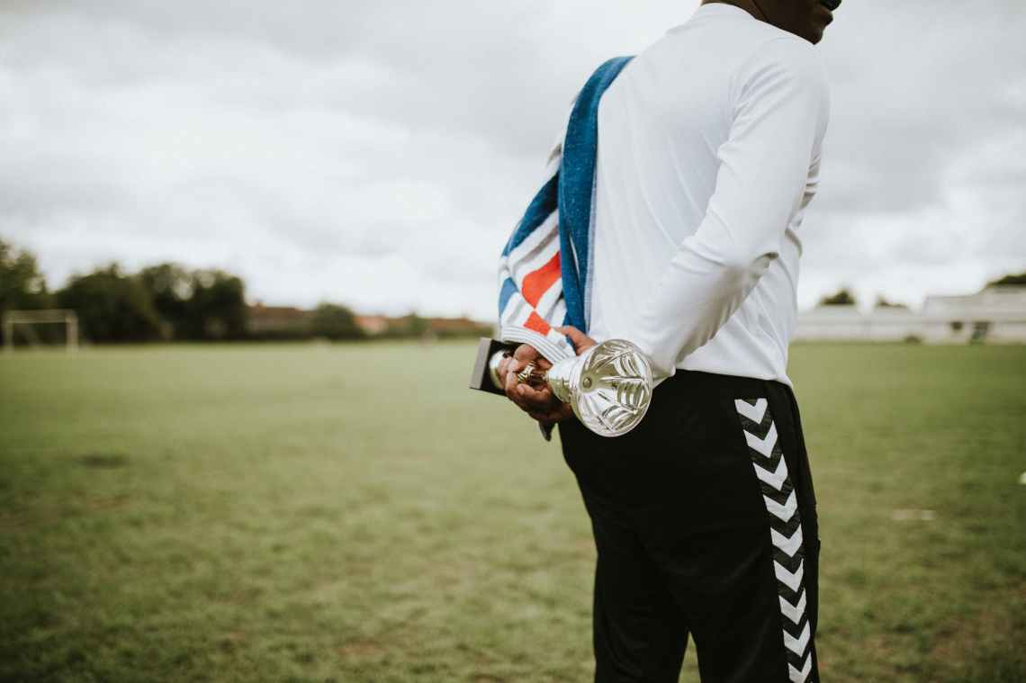 man holding silver trophy